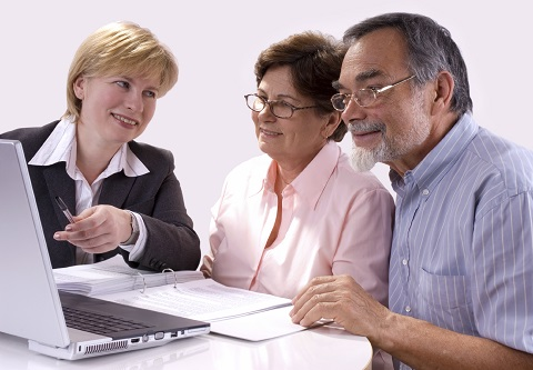 Older Couple Looking at Laptop with Agent