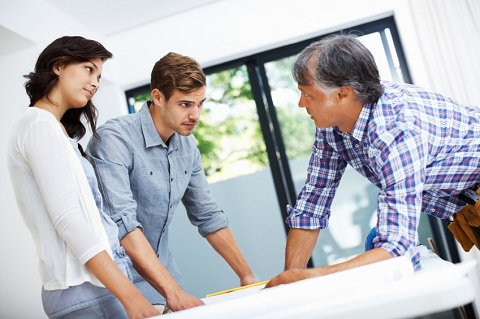 Young Couple Looking Over Floor Plans With Builder